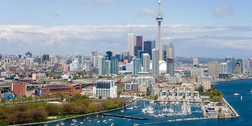 مهاجرت به کانادا علاقمند به دریافت اقامت کانادا هستید؟ آیا برنامه های مهاجرتی این کشور را می شناسید؟ چقدر با کانادا آشنایی دارید؟ شما میتوانید برای پاسخ به سوال های خود ادامه مقاله را مطالعه کنید.کشور کانادا با حدود 36 میلیون نفر جمعیت، در قاره آمریکای شمالی قرار دارد. این کشور دومین کشور وسیع جهان هست. کانادا منابع طبیعی فراوانی دارد و آب و هوای بیشتر قسمت های این سرزمین سرد است. اصلی ترین منبع اقتصاد کانادا از صنعت گردشگری، بخش کشاورزی و پتروشیمی به دست می آید. با وجود مکان های طبیعی و تفریحی فراوان، کانادا جزو 15 کشور دیدنی دنیا با آمار گردشگری بیش از 20 میلیون نفر در سال است.همچنین کشور کانادا یکی از مهاجرپذیر ترین کشور های جهان می باشد. در سال هایی که برخی کشورهای جهان درهای مهاجرت خود را به سوی مهاجرن بسته اند، کانادا برای رشد اقتصادی خود و جلوگیری از بالا رفتن میانگین سنی کشور سالانه صد ها هزار مهاجر توانایی که در روند رشد اقتصادی کشور مفید هستند را پذیرش می کند. از برنامه های مهاجرتی این کشور میتوان به برنامه تخصص کاری، سرمایه گذاری، کارآفرینی، اکسپرس انتری و … اشاره کرد. میتوان گفت معروفترین و پر تقضاترین برنامه مهاجرت به این کشور، برنامه اکسپرس انتری است. کانادا در سال 2015 از این سیستم رونمایی کرد. این برنامه به استان های کانادا کمک می کند که به نسبت نیاز بازار کار خود مهاجران واجد شرایط را کاندید دریافت اقامت دائم کانادا کنند. همچنین در برنامه اکسپرس انتری سرعت پذیرش مهاجران بسیار بیشتر است. کشور کانادا جدا از بخش مهاجرت، جزوی از برترین کشور های جهان برای تحصیلات است. تحصیل در کانادا کمک شایانی به دانش آموزان و دانشجویان می کند زیرا در این کشور بخش های آموزشی (مدارس،دانشگاها، کالج ها و …) با سیستم های بروز، امنیت فوق العاده و همچنین مدارکی بین المللی در تلاش هستند تا آینده بهتری برای افراد بسازند.